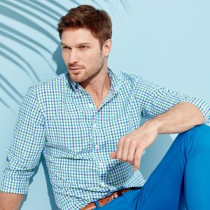 man sitting in checkered shirt with blue pants